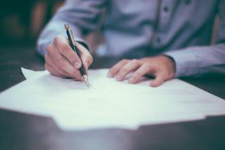 Man signing school expulsion agreement