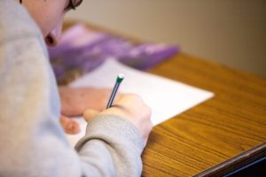Girl writing on IEP document